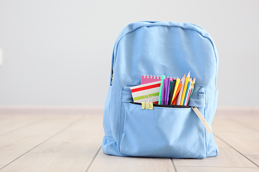 school backpack and stationery in a bright room. Preparing for school. Back to school. Place for text. National School Backpack Awareness Day