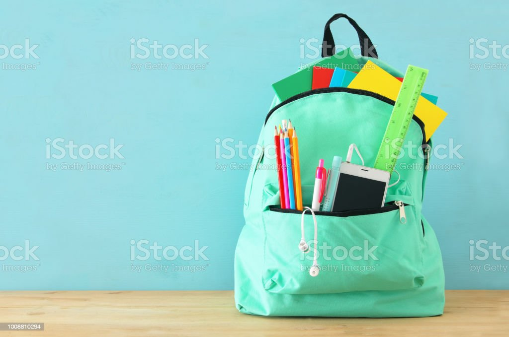 school bag with stationery and notebooks in front of wooden blue background. Back to school concept. royalty-free stock photo