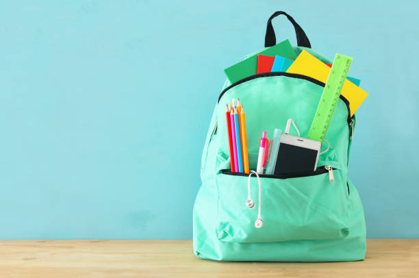 school bag with stationery and notebooks in front of wooden blue background. back to school concept. - school supplies stock pictures, royalty-free photos & images