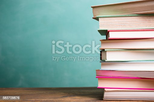 istock School books stacked on desk with chalkboard. 583709876