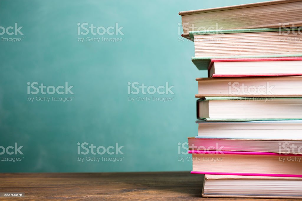 School books stacked on desk with chalkboard. stock photo