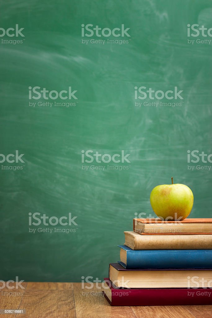 School books with apple on desk stock photo