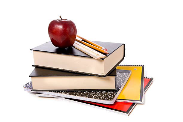 School Books with Apple A stack of school books and spiral notebooks with a pencil and a ruler on top in front of a white background with an apple textbook stock pictures, royalty-free photos & images