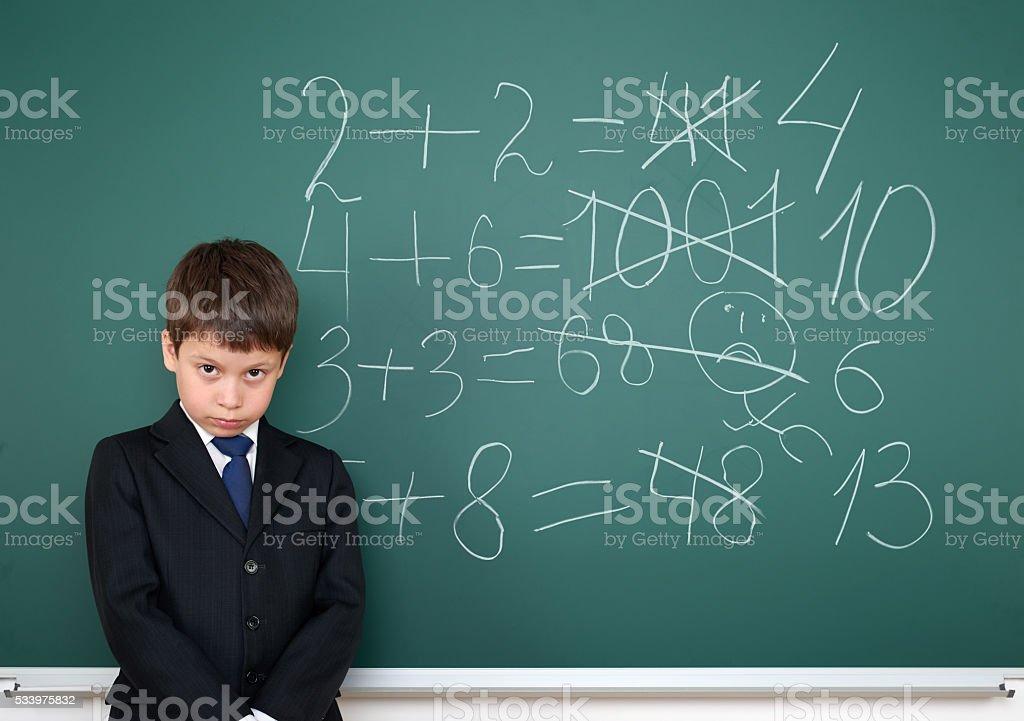 school boy decides examples math on chalkboard, education exam stock photo