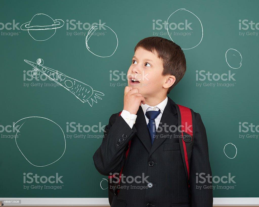 school boy drawing space rocket on board stock photo