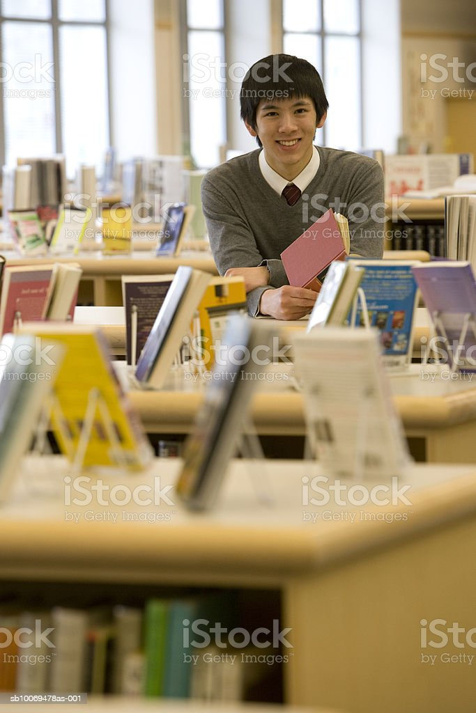 School boy holding book in library, portrait 免版稅 stock photo