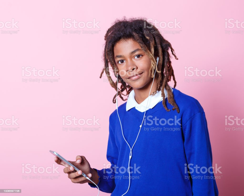 School boy listening to music from mobile phone Portrait of teenage school boy listening to music from mobile phone. Afro american student in school uniform listening to music with smart phone. 12-13 Years Stock Photo