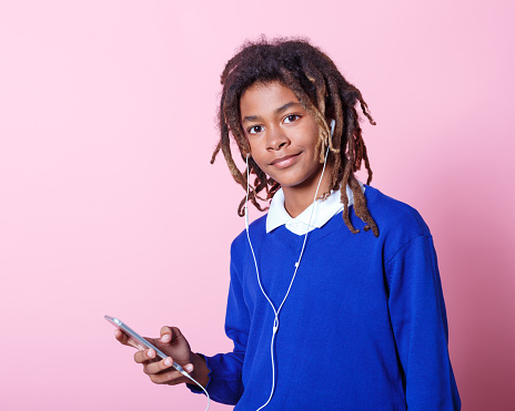 School Boy Listening To Music From Mobile Phone Stock Photo - Download Image Now