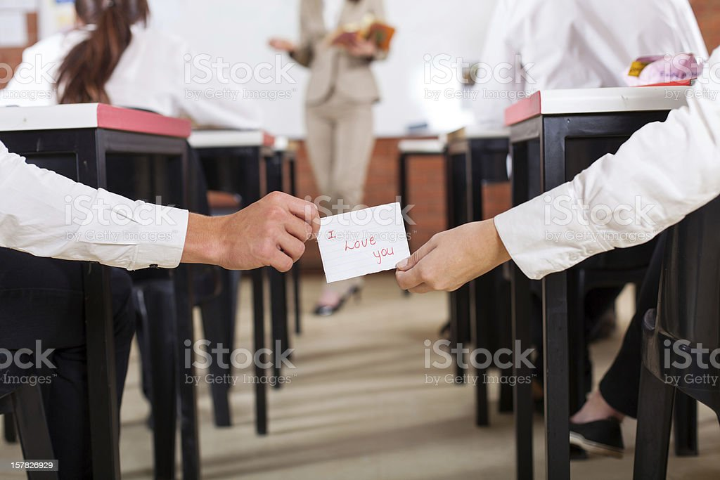 school boy passing I Love You note to a girl royalty-free stock photo