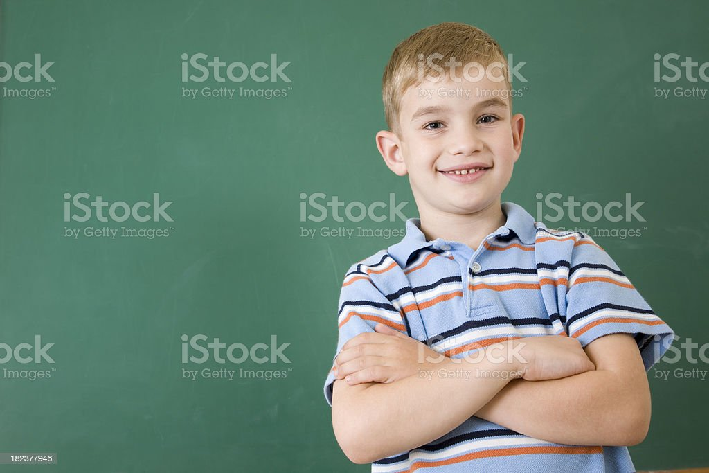 School Boy Proudly Standing in front of Chalkboard royalty-free stock photo