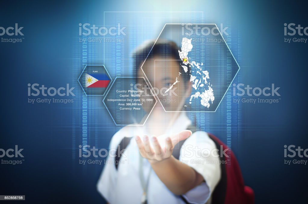 School boy showing facts about the Philippines through virtual screen hologram technology. stock photo