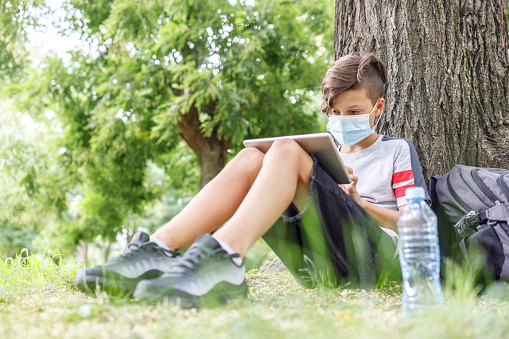 Child wearing protective mask when reading e-book at the park
