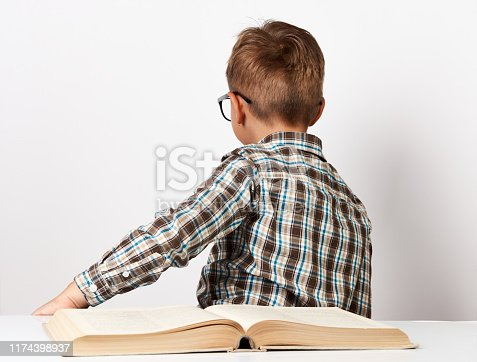 istock School boy sitting turn back at the table with school book 1174398937