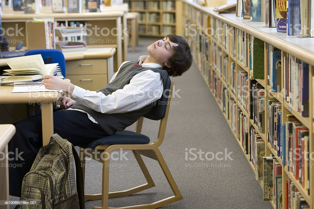 School boy (16-17) sleeping at desk in library royalty-free stock photo