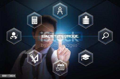 istock School boy touching Back to school button using Virtual Screen Hologram 688173604