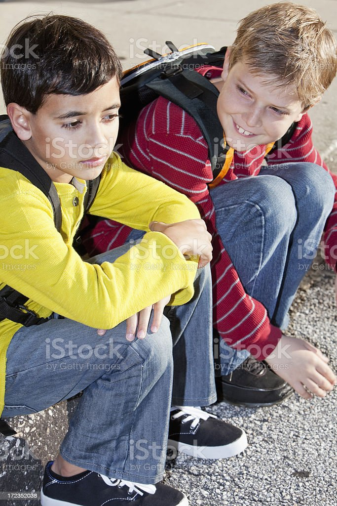 School boy trying to cheer up friend stock photo