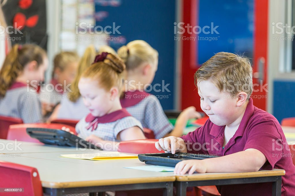School Boy Using A Tablet Computer In The Classroom stock photo