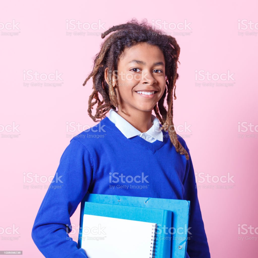 School boy with books Portrait of happy young student with books in hand over pink background. Afro american kid in school uniform looking at camera and smiling. 12-13 Years Stock Photo