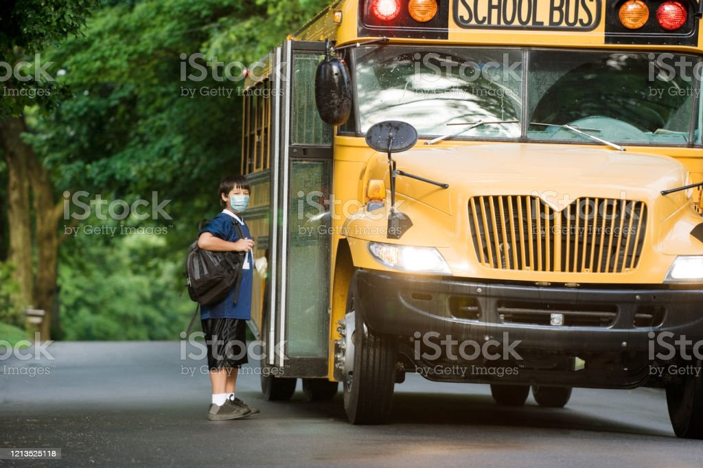 school boy with surgical mask at bus stop. School bus picking up elementary student wearing surgical mask boarding at bus stop. 10-11 Years Stock Photo