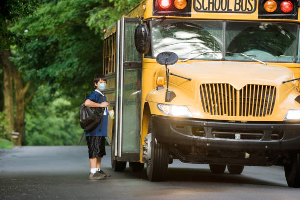 school boy with surgical mask at bus stop. School bus picking up elementary student wearing surgical mask boarding at bus stop. school buses stock pictures, royalty-free photos & images