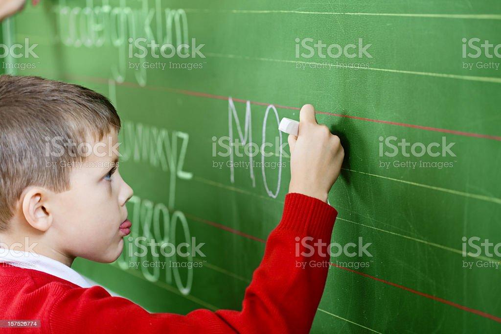 School Boy Writing On Blackboard, Side View royalty-free stock photo