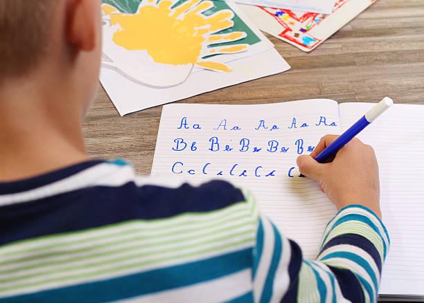 schule junge schreiben auf papier mit stift auf einen bestimmten buchstaben. - hard to concentrate stock-fotos und bilder