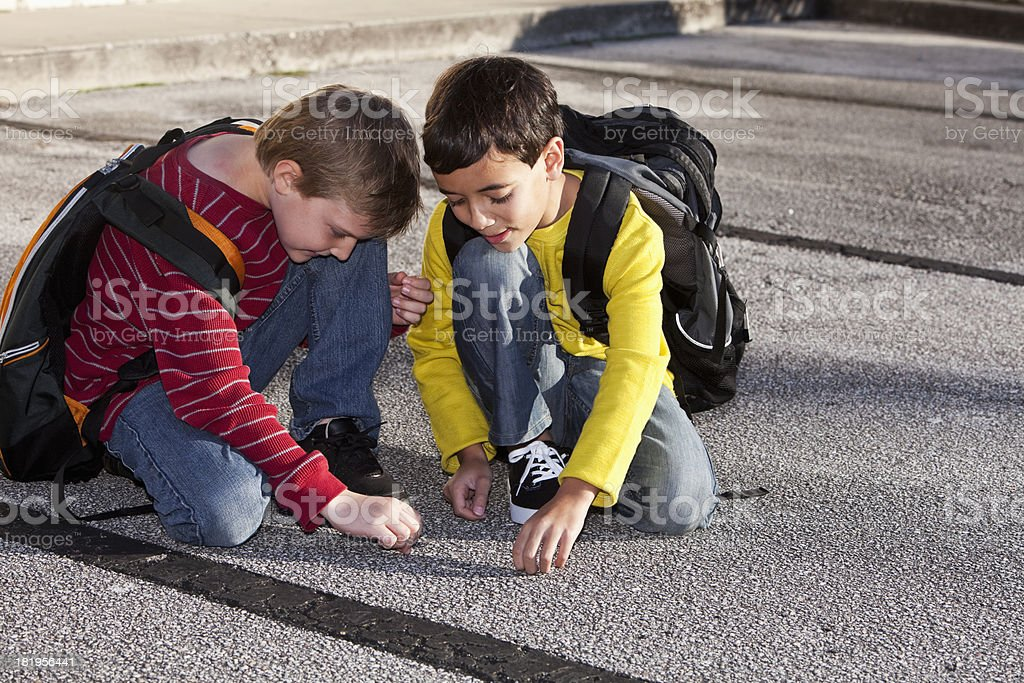 School boys kneeling on the ground, playing stock photo