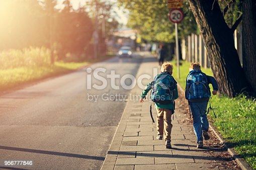 Two school boys running on sidewalk on way to school. Sunny day morning. Shot with Nikon D850