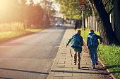 Two school boys running on sidewalk on way to school. Sunny day morning.\nShot with Nikon D850