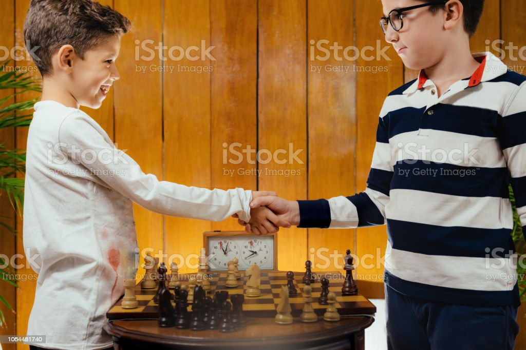 Chess for children. School boys shaking hands after a game of chess.