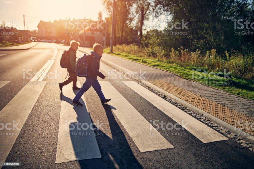 Jongens van de school lopen op zebrapad op weg naar school - Royalty-free 8-9 jaar Stockfoto