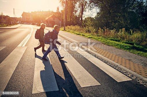 Two school boys walking on zebra crossing on way to school. Sunny day morning.