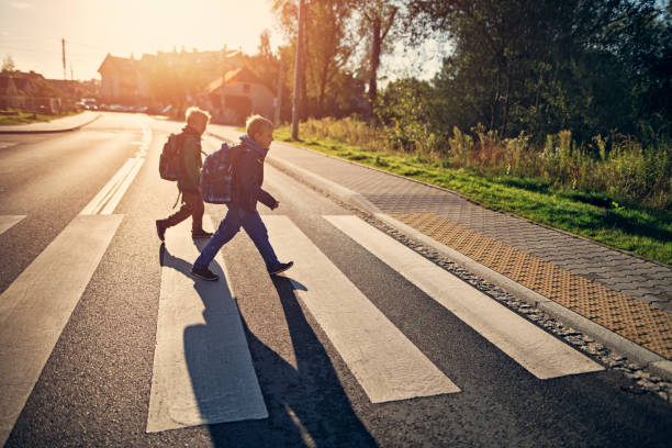 School boys walking on zebra crossing on way to school stock photo