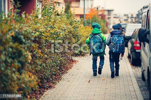 Two school boys walking on sidewalk on way to school. Cloudy autumn day. Shot with Nikon D850