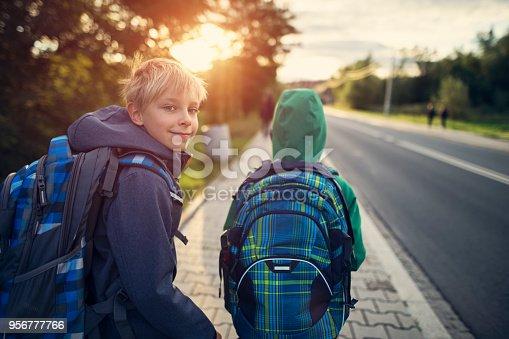 Two school boys walking on sidewalk on way to school. Sunny day morning. Shot with Nikon D850