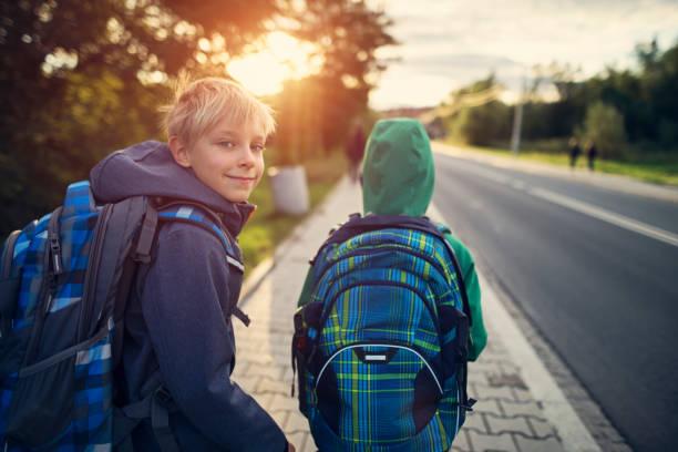 school boys walking to school - scolaro foto e immagini stock