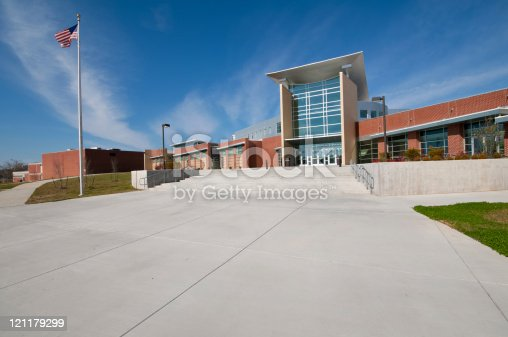 this color image is of a School Building or Business Building with American Flag. the building could also be a library or mall or church or university or gymnasium. the architecture is very modern. there is a massive sidewalk or walkway to the building. and the entrance is made of glass. the building is made of brick, glass and cement. there is also a lawn that is of green grass. and the lighting is natural sunlight. and the background is blue sky with white clouds.