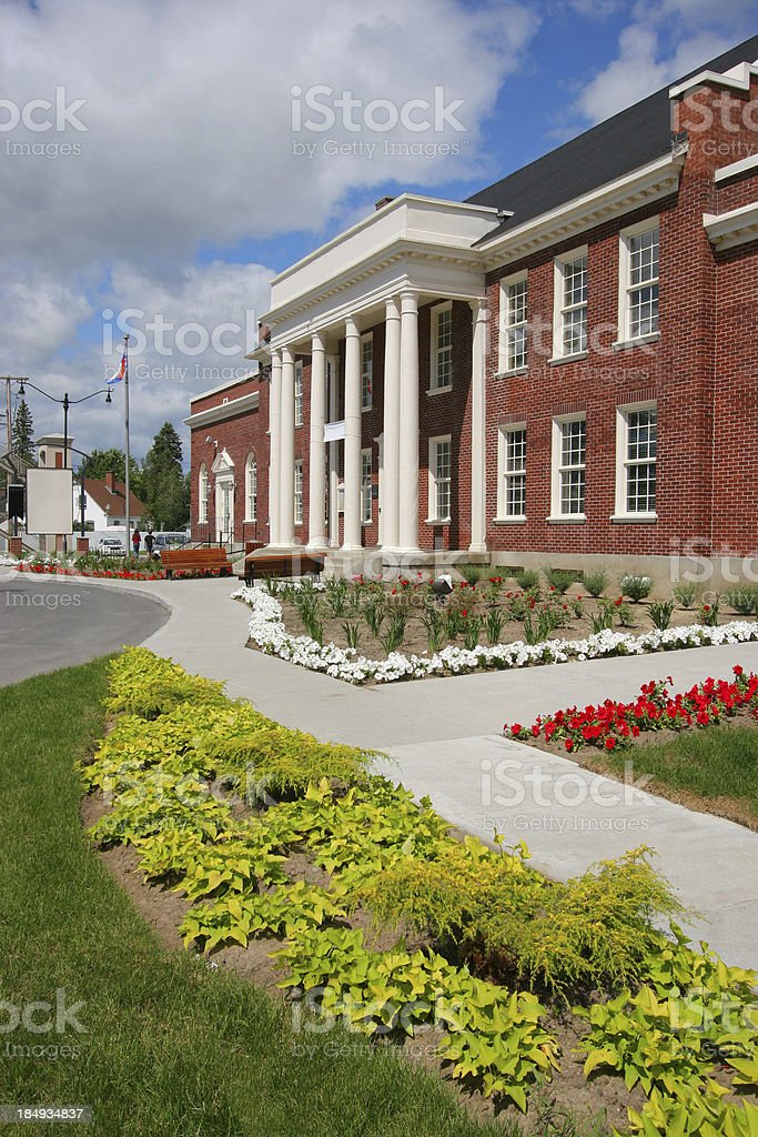 School building with columns and flowers stock photo