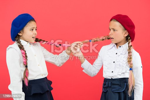 School bullies. Bully girls on pink background. Bully classmates pulling pigtails at school. Bully or bullied.