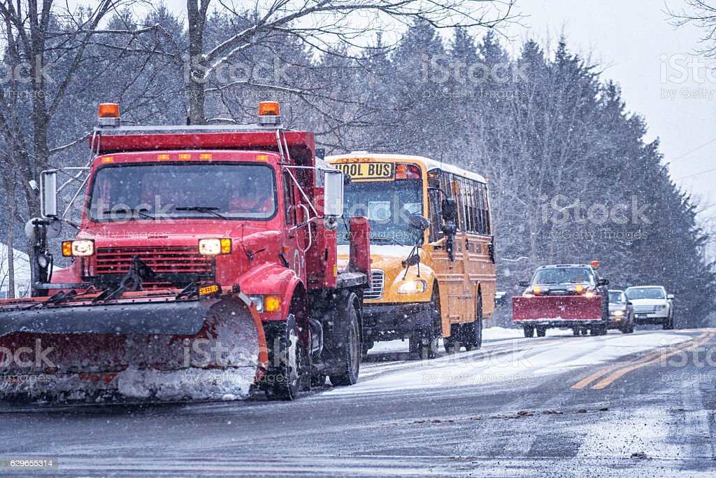 School Bus And Snowplow Trucks in Blizzard Snow Traffic stock photo