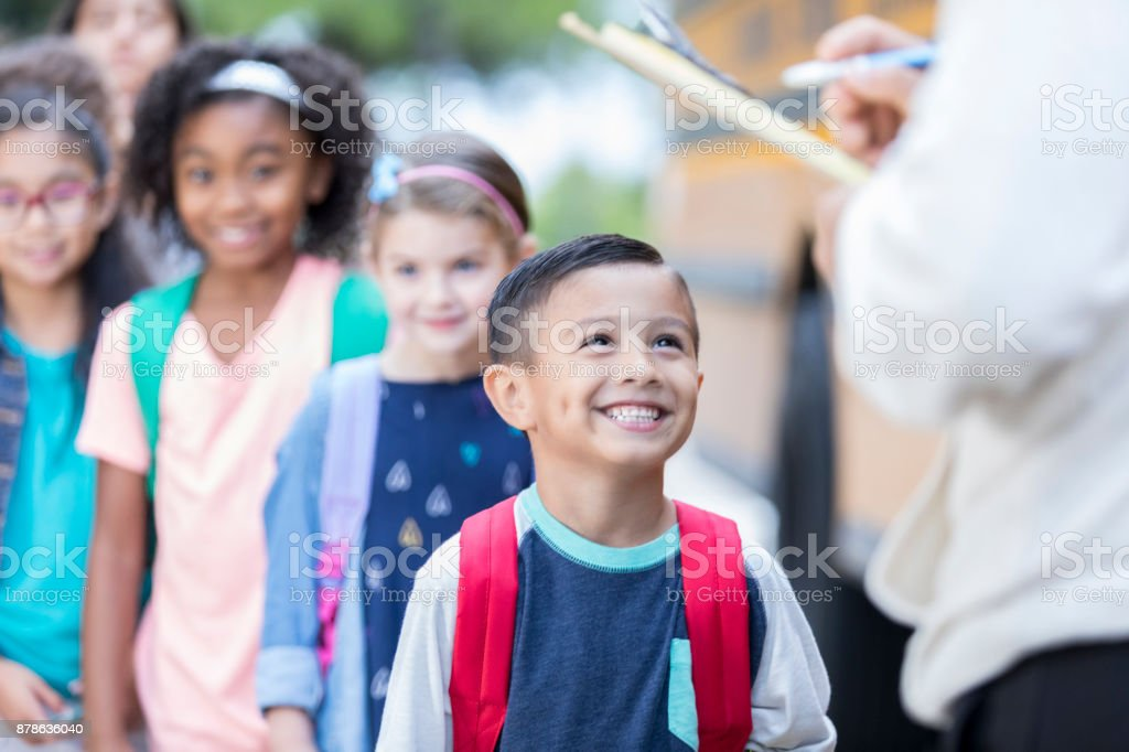 School bus driver checks children off as they get on bus stock photo