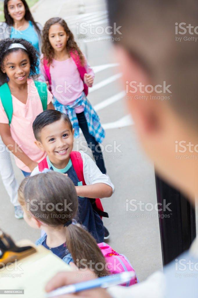School bus driver greets school children stock photo