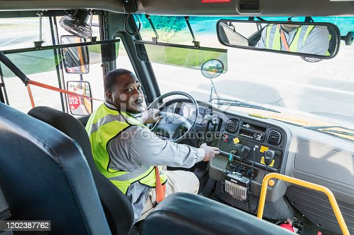 A mature African-American man working as a school bus driver, sitting in the driver's seat wearing his seat belt and a reflective vest, looking over his shoulder at the camera. The bus stop sign is visible in the side view mirror.