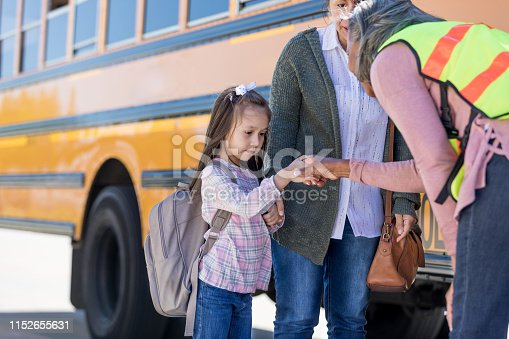 At the school bus stop, a shy schoolgirl looks down at the ground as the school bus driver leans down to shake her hand.