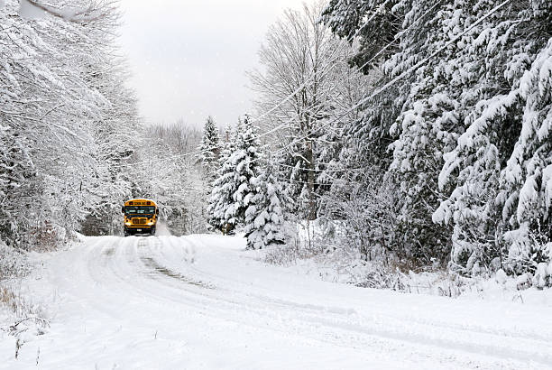 School Bus Drives On Snow Covered Rural Road stock photo
