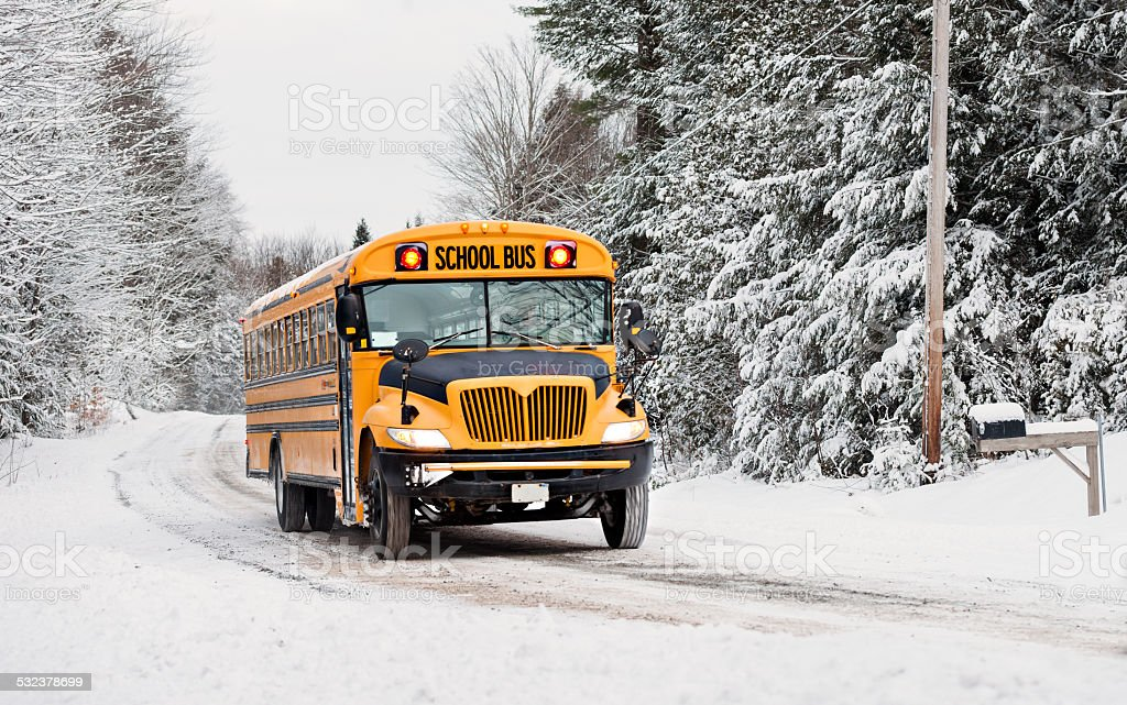 School Bus Driving Down A Snow Covered Road stock photo