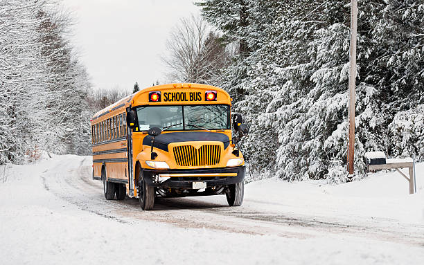 school bus driving down a snow covered road - school buses stock pictures, royalty-free photos & images