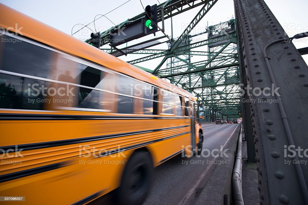 School bus is moving on bridge with green traffic light stock photo