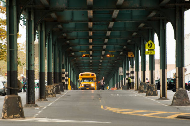 un autobús escolar está pasando bajo el puente del tren en el bronx, nueva york, estados unidos. - suministros escolares fotografías e imágenes de stock