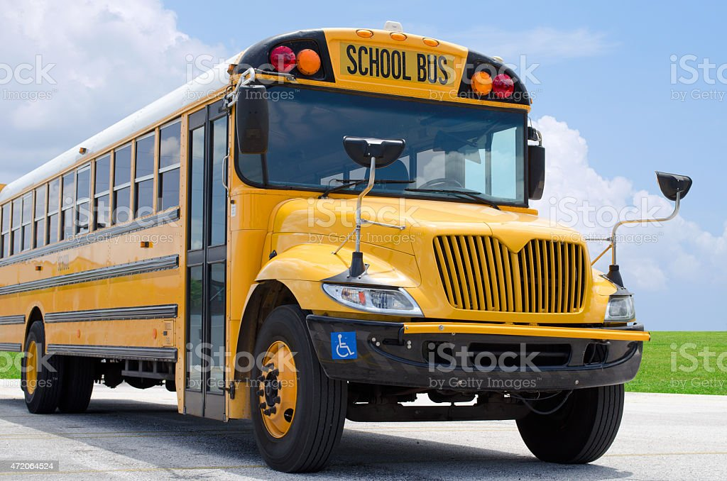 School bus on blacktop with clean sunny background stock photo